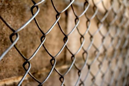 image of blur rusty net fence near old brick wall photo