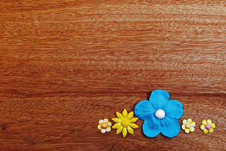 yellow and blue  paper flower on wooden background Stock Photo