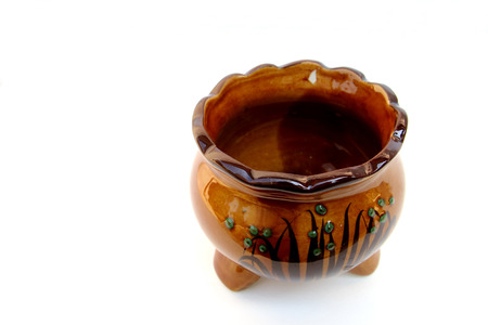 a jar stand: brown ceramic joss pot on white background in soft focus
