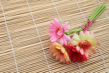 matt: bunch of artificial flower on bamboo matt in soft focus Stock Photo