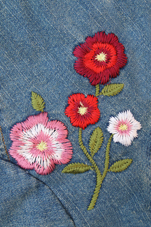 the embroidery: bordar flor en pantalones vaqueros Foto de archivo