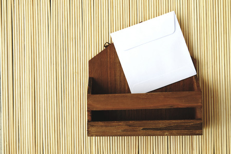 old envelope: image of small letter box and white envelope on bamboo matt