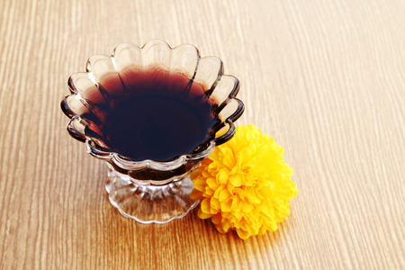 grape juice in glass on wooden background in soft focus photo