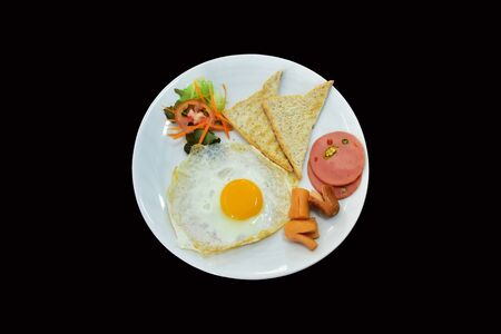 breakfast set on white plate,fried egg ,bread,ham,sausage and some vegetable.top view image.