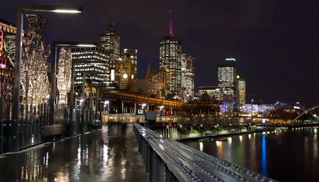 The City of Melbourne, at night, looking from a bridge over the Yarra, back over the city skyline with Flinders Street Station all lit up and reflections in the puddles