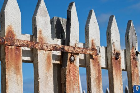 ravaged: A white fence, stained with rust and ravaged by the weather