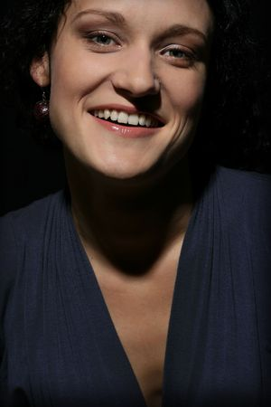 Young happy laughing woman over black background photo