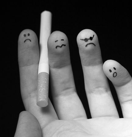 Black and white photo of fingers holding cigarette. Sad smiley painted on fingertips. Conception of addiction and anti-smoking. photo