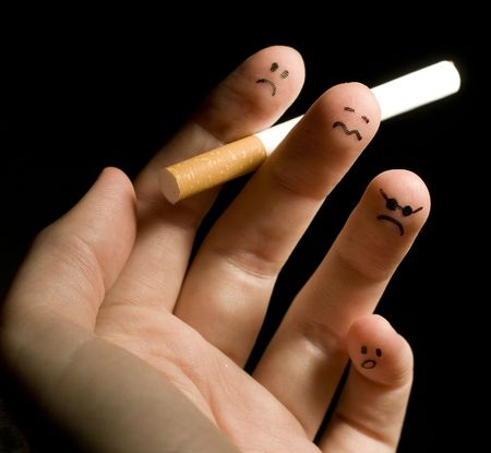 decease:   Fingers holding cigarette. Sad smiley painted on fingertips. Conception of addiction and antismoking.