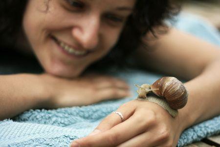 slowly: Mujer de celebración de caracol sobre su mano y sonriendo  Foto de archivo
