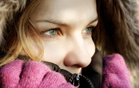 Beautiful young woman wearing winter jacket hood and gloves photo