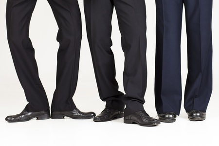 caballeros: Tres patas de negocios sobre fondo blanco haciendo posturas chistosas. Foto de archivo