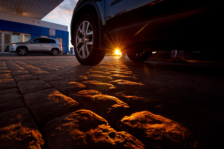 Western Siberia, Russia. 08042018. The car stopped at a petrol station on the Chui tract. Going beyond the horizon, the sun surprisingly lit up the cobblestone road surface. Редакционное