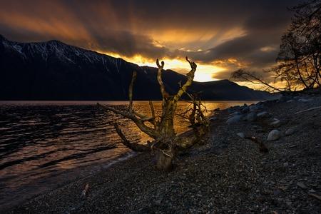 Spring sunset on a mountain lake. Russia. The South Of Western Siberia. Mountain Altai. Spring dawn on the shore of the lake Teletskoye.