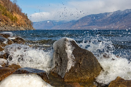 The beating waves on the rocks. Russia. mountain Altai. Early spring in the South of the lake Teletskoye.