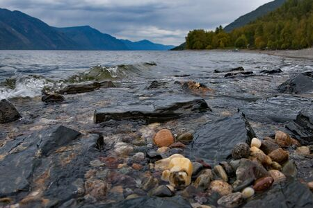 The colorful rocky shores of a mountain lake. Russia. South Of Western Siberia, Altai Mountains. Altai state natural biosphere reserve, Bele cordon in the South of lake Teletskoye