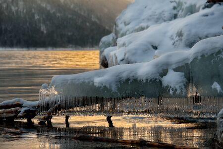 Russia. mountain Altai. Evening light in ice floods and icicles on the shore of lake Teletskoye.