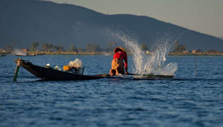 The Inle Lake. Myanmar. 11/27/2016. At sunset the fishermen are fishing in an unusual way - standing on the edge of the boat and driving the paddle leg, cast net and drive the fish strikes the water.
