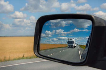 Samara. Russia. August 16, 2018. The reflection of a truck moving along the Samara-Ufa federal highway in the side mirror of the car. Sajtókép