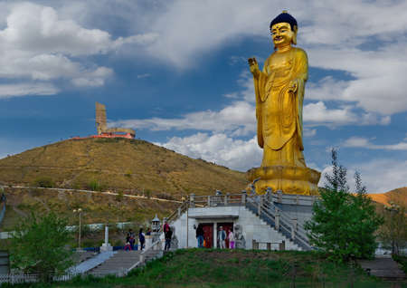 Ulaanbaatar. Mongolia. June, 08, 2015. Golden Buddha statue in the park at the foot of Mount Zaisan with a memorial in memory of the Soviet soldiers who died on the Khalkhin-Gol River. Sajtókép