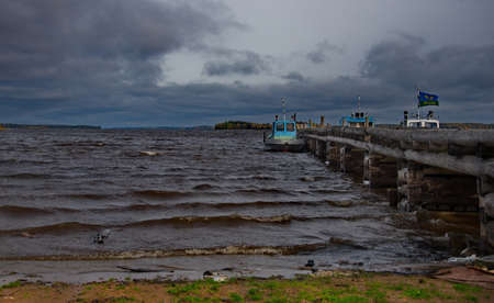 Kuganavolok. Russia. October 04, 2018. Boats on the old wooden pier of Lake Vodlozero in the village Republic of Karelia.