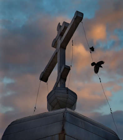 Russia. Republic of Karelia. Crows over the cross of an abandoned Orthodox church on the shore of Lake Onega. Stock fotó