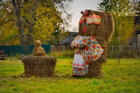 Nikolskoye. Russia. October 07, 2018. Sculptures of peasants from bales of mown hay, installed in honor of the successful completion of the haymaking season on the shore of Lake Kubensky.
