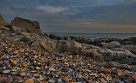 Russia. Dagestan. Dawn on the rocky shore of the Caspian Sea, strewn with many shells, near the city embankment of the city of Makhachkala.