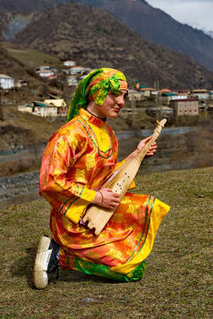 Tliarata. Russia. April 07, 2021. A young girl in national clothes plays the tamur against the background of the Caucasus Mountains. This is a unique two-stringed musical instrument of Dagestan.
