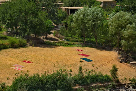 Afghanistan. Washed woven carpets dry in the sun on a stony plot of land on the bank of the border Panj River.