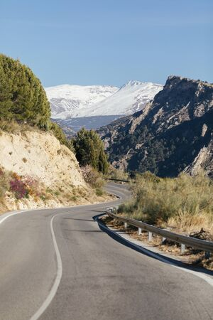 Road through the Spanish Sierra Nevada in Andalusia with a snowy mountain in the background