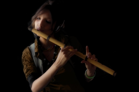 Beautiful exotic young woman playing flute photo