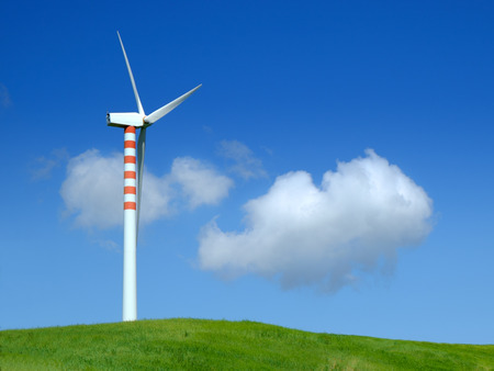 Wind turbine in a green field with blue sky and clouds photo