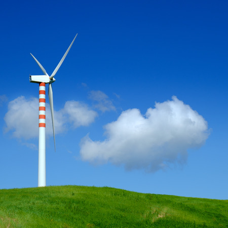 Wind turbine in a green field with blue sky and clouds Stock Photo