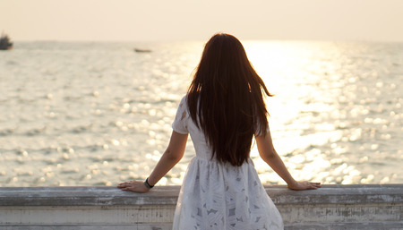 Girl watching sea and sunset on a balcony photo