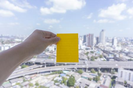 sticky hands: Green sticky note put on urban scene with sky