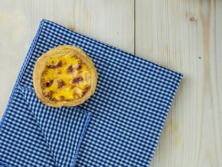 scott: Egg tart on wood table with scott pattern napkin Stock Photo