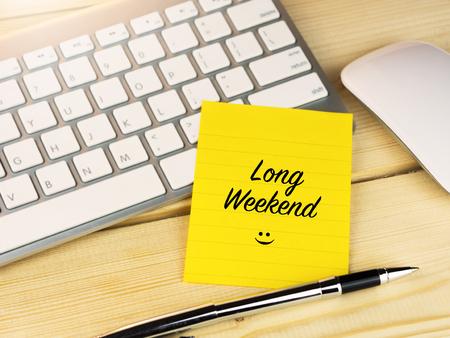 long weekend: Long weekend on sticky note on work desk