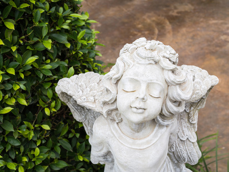 White Cherub sculpture with wings and closing eyes Stock Photo
