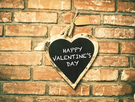 valentine s day beach: Happy valentines day on heart shape chalkboard on concrete wall
