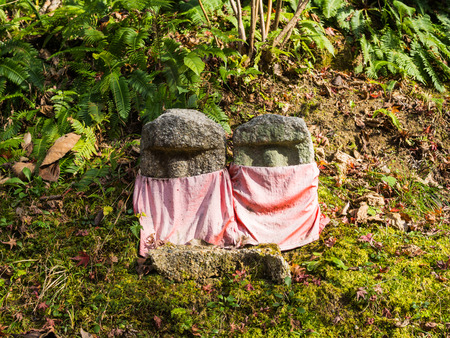 Small stone covered by scarfs in winter in Japanese temple, Japan Stock Photo