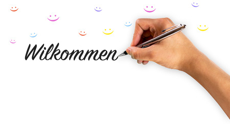 welcome mat: Wilkommen with hand writing and smiley faces in many colors Stock Photo