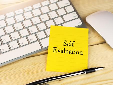 Self evaluation on sticky note on work desk Stock Photo