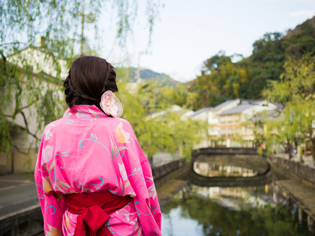 Girl dressing Kimono watching weeping willow tree and village Stock Photo