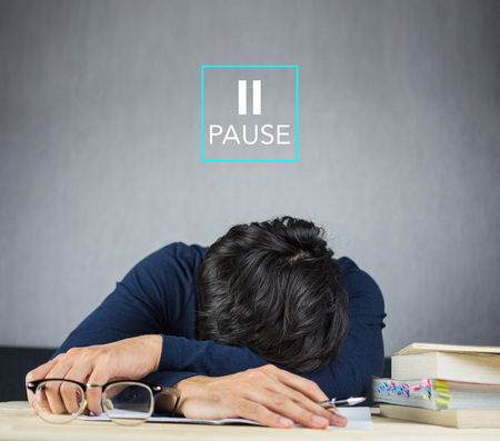Pause sign and man falling asleep while studying on the desk