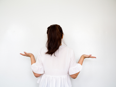 Girl opening hands, Shrug and careless gesture on white background Stock Photo