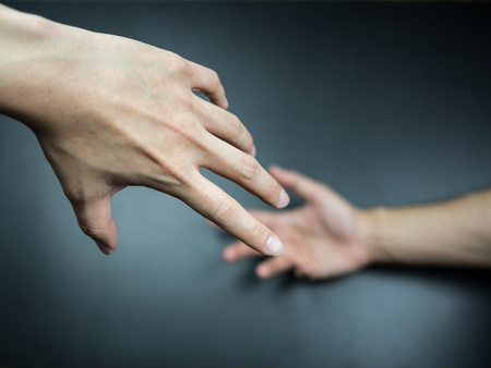 Hands reaching to each other on background Stock Photo
