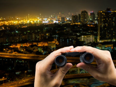 Binocular on hand holding and cityscape at night