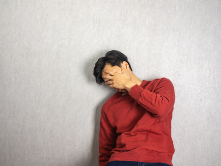 Man covering face back against the wall