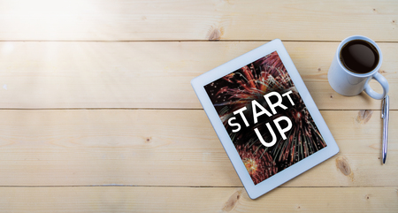 Start up text on tablet on wooden work table Stock Photo